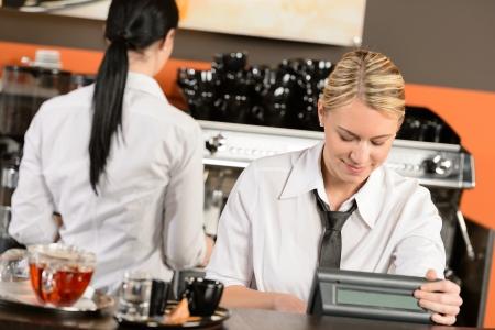 Serveuses heureux de travailler à café en uniforme