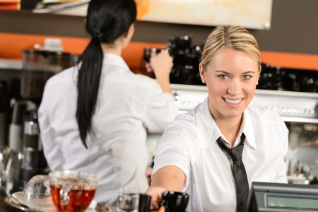 cashier: Young happy waitress cashier giving coffee in cafe