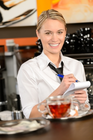 Smiling waitress taking order in coffee house looking at camera Stock Photo - 19379836