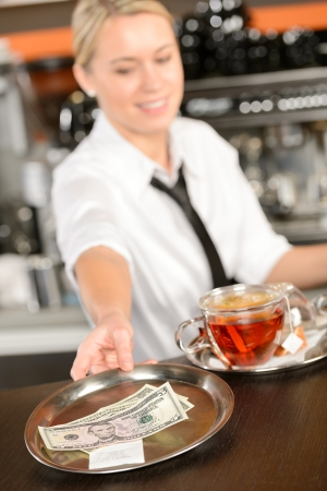 Attractive waitress taking tip in bar from tray american dollar photo