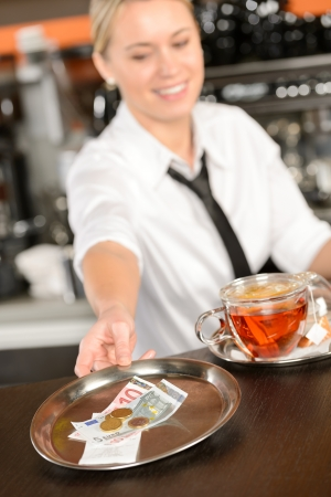 Attractive waitress taking tip in bar from tray euro photo