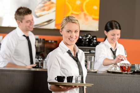 Confident waitress serving coffee with tray colleagues working behind photo