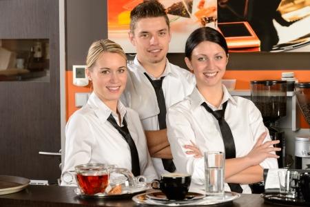 Three smiling server posing in uniform in cafe