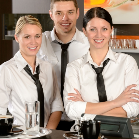 Three smiling server posing in uniform in cafe photo