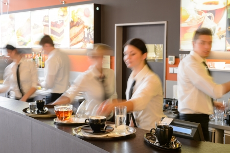 číšník: Busy číšník a servírky pracují v baru v noci