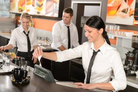 coworker: Female cashier giving receipt colleagues working in cafe
