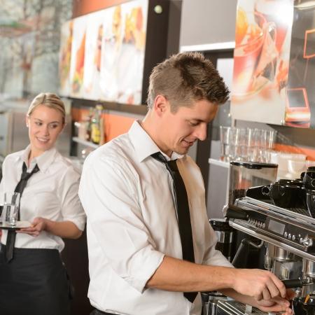 číšník: Mladý číšník a servírka pracuje v baru porce kávy