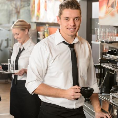 Camarero hermoso que hace caf� con m�quina de caf� espresso en la cafeter�a photo