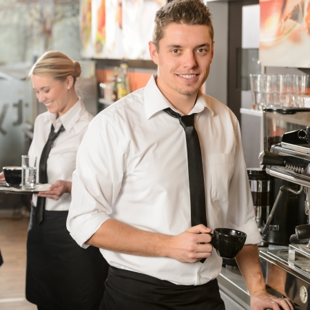 Handsome waiter making coffee with espresso machine in coffee house photo