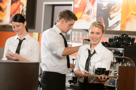 barista: Confident waitresses and waiter working in bar serving drinks