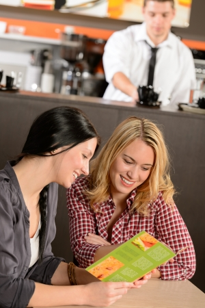 Two young female customers reading menu in pub Stock Photo - 19379815