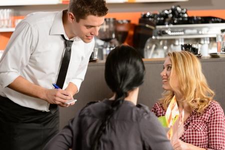 číšník: Číšník přijímá objednávky od mladé ženy zákazníka v restauraci