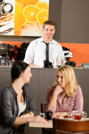 Attractive bartender smiling in pub female customers talking Stock Photo - 19379804