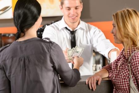 Clientèle féminine payer par dollar de trésorerie dans la barre de barman Banque d'images