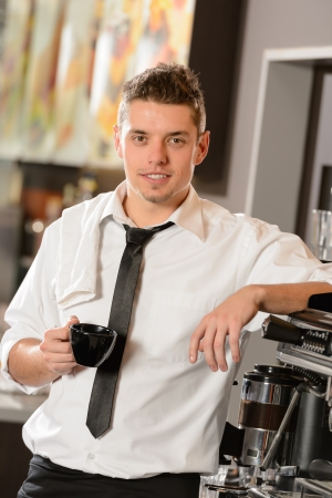 Attractive waiter leaning on espresso machine drinking cup of coffee photo