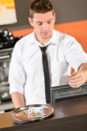 Jeune barman en uniforme tenant cash euros en bar Banque d'images