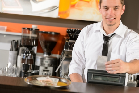 Handsome smiling male waiter giving receipt czech crowns in pub