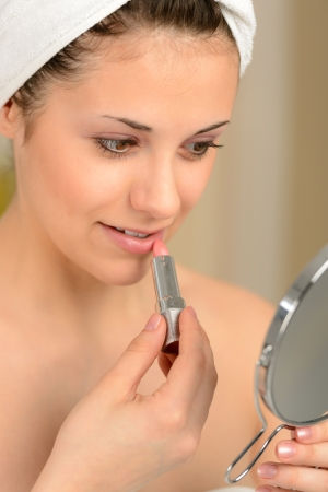 Young teenager girl using lipstick with handheld mirror Stock Photo - 19379793