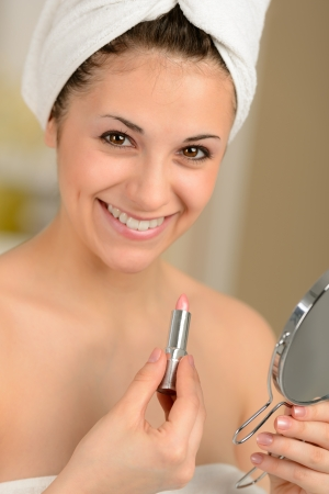 Smiling young woman applying lipstick with mirror wrapped in towel Stock Photo - 19379792