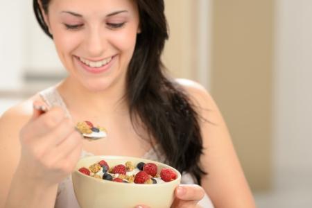 comiendo cereal: Mujer alegre que come el cereal sano para el desayuno