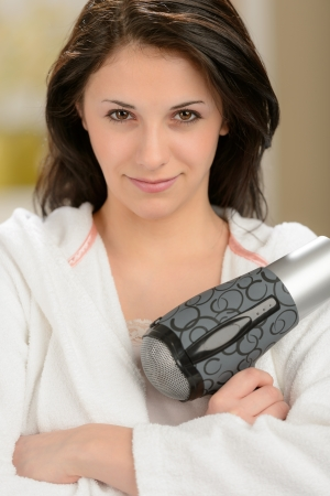 blow dryer: Confident girl posing with blow dryer in bathrobe