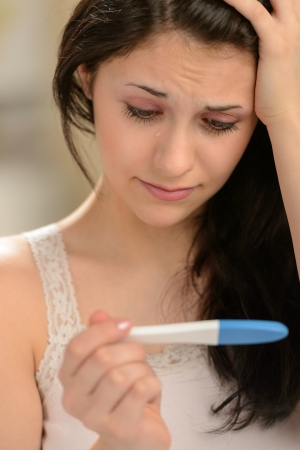 pregnancy: Distraught girl waiting for pregnancy test result thinking about future Stock Photo