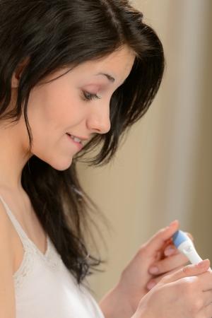 womanhood: Surprised happy girl looking at pregnancy test