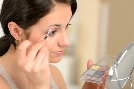 putting on: Young girl applying eyeshadow on eyelid looking at mirror