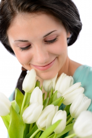 Smiling delighted woman holding bouquet of white tulips photo
