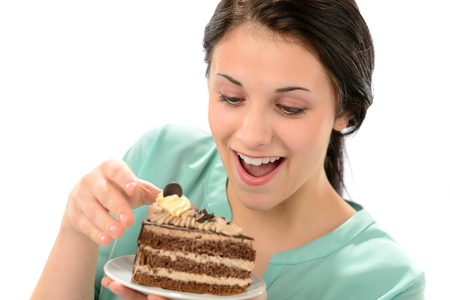 indulging: Joyful young girl eating tasty piece of cake Stock Photo