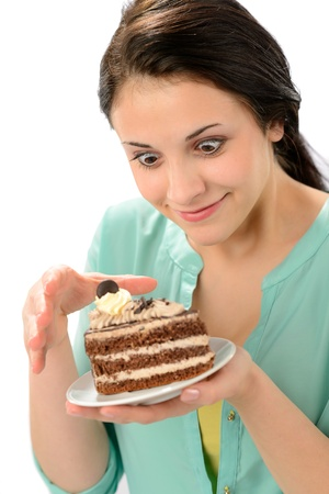 Tempting sweet piece of cake and young hungry woman photo