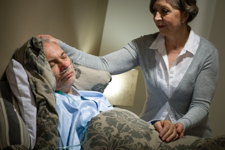 Sick lying senior woman with caring husband at home photo