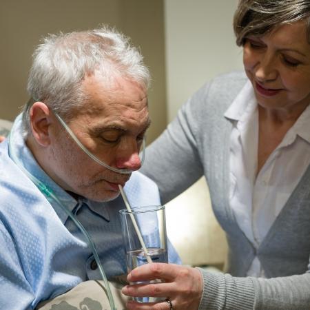 Amamantar ayuda a un enfermo de alto nivel con beber vaso de agua Foto de archivo
