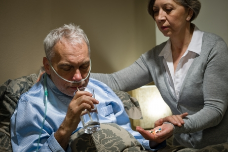 taking a wife: Senior man taking medication with water caring wife helping