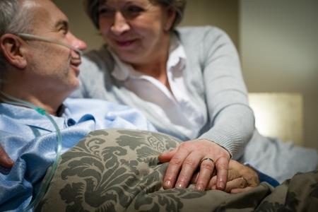 Ancianos pareja de la mano al enfermo en la cama