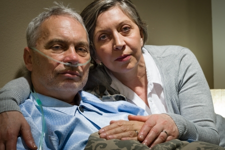 worried woman: Anxious senior wife holding her sick husband at clinic