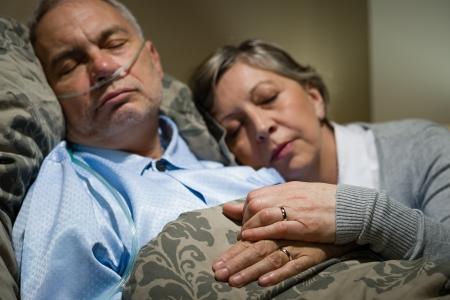 Antigua pareja durmiendo juntos en la cama hombre con cánula nasal