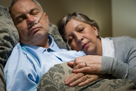 Old couple sleeping together in bed man with nasal cannula Stock Photo