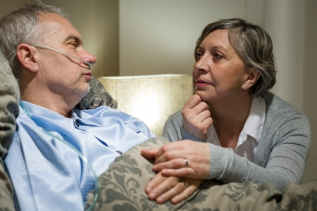 Senior patient at hospital with worried wife holding hands Stock Photo