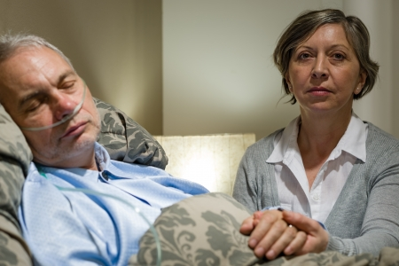 Caring wife holding sick senior husband's hands lying in bed