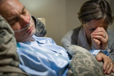 Old mujer orando por una enfermedad terminal marido tumbado en coma