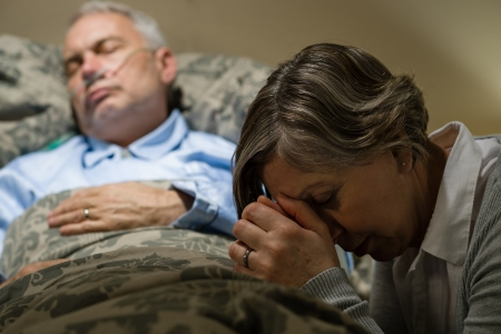 Senior woman praying for sick man sleeping in hospital bed