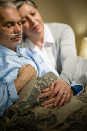 Loving elderly couple sleeping in bed sick husband photo