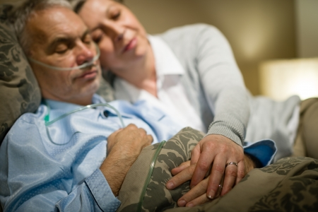 bedside: Retired ill man and caring wife sleeping together holding hands