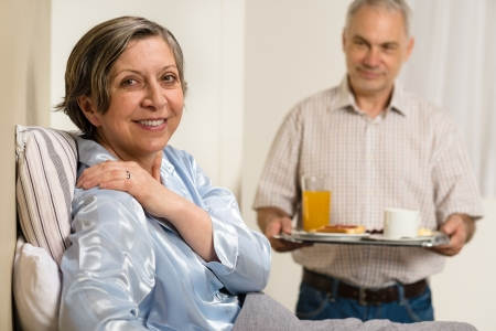Caring senior man bringing breakfast to her sick wife photo
