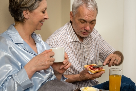 Elderly couple eating romantic breakfast together in bed photo