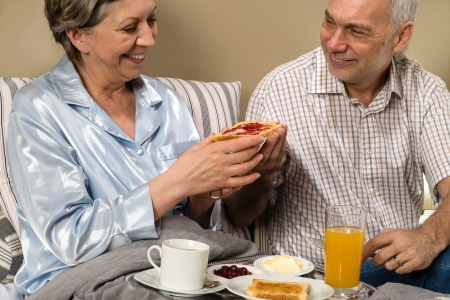 Senior couple having romantic morning breakfast in bed photo