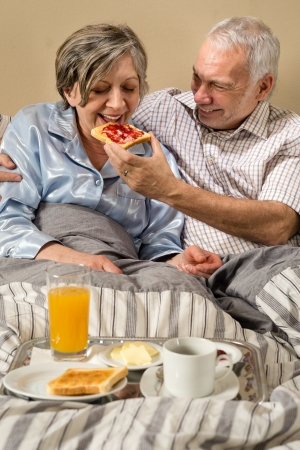 Senior couple lying in bed man feeding breakfast to woman photo