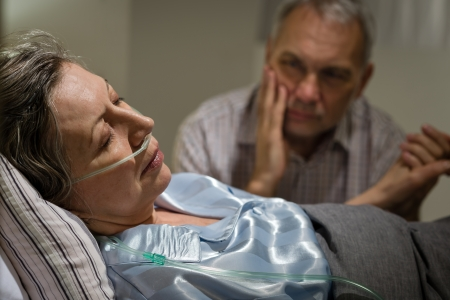 hospice: Sick mature woman lying in bed worried husband holding hands