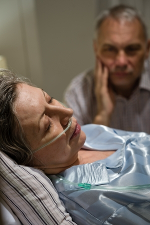 the unconscious: Dying old woman in hospital bed with caring man